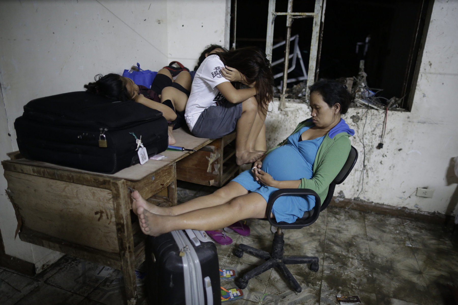 TACLOBAN, PHILIPPINES - NOVEMBER 17: Victims waiting to for a flight out wait at the airport to board a C130 after midnight in Tacloban, Philippines November 17, 2013. Typhoon Haiyan devastated the region with estimated death toll of around 10,000.