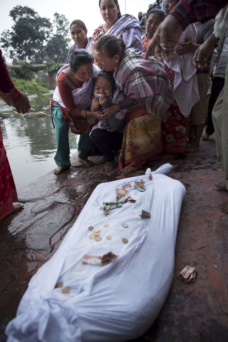 Bhaktapur, Nepal - May 8, 2015: Relatives mourn the death of Kiran Prajapati,40, who was found in the ruins of a Kathmandu building 13 days after the earthquake. He was cremated in Bhaktapur where he was from.