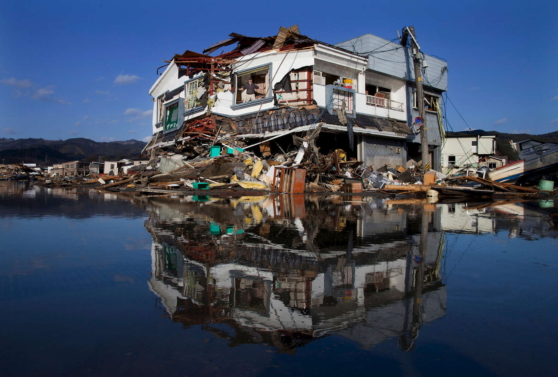 Toyoki Sugawara  looks out from his destroyed liquor shop where he is collecting the items he can salvage March 18, 2011 in Kesennuma, Japan.  One of the world\'s most developed country suffered it\'s worst natural disaster as a strong 8.9 earthquake followed by a Tsunami hit the north-central coast of Japan, killing thousands, followed by a potential nuclear meltdown after the country\'s major nuclear plant was seriously damaged from the quake.