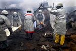 Rescue workers carry a charred body from the rubble of a village destroyed by the devastating earthquake, fires and tsunami March 16, 2011 in Kesennuma, Miyagi province, Japan.  One of the world\'s most developed country suffered it\'s worst natural disaster as a strong 8.9 earthquake followed by a Tsunami hit the north-central coast of Japan, killing thousands, followed by a potential nuclear meltdown after the country\'s major nuclear plant was seriously damaged from the quake.
