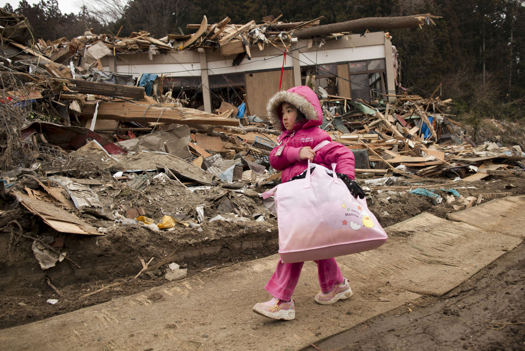 Neena Sasaki, 5, carries some of the family belongings from her home that was destroyed after the devastating earthquake and tsunami March 15, 2011 in Rikuzentakata,  Miyagi province, Japan.  One of the world\'s most developed country suffered it\'s worst natural disaster as a strong 8.9 earthquake followed by a Tsunami hit the north-central coast of Japan, killing thousands, followed by a potential nuclear meltdown after the country\'s major nuclear plant was seriously damaged from the quake.