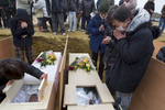 Families and relatives of the dead cry as they identify their family members at a temporary burial ground March 25, 2011 in Higashi Matsushima , Japan.  Under Japanese Buddhist practice a cremation is the expected traditional way of dealing with the dead but now with the death toll so high crematoriums are overwhelmed and there is a shortage of fuel to burn them. Local municipalities are forced to dig mass graves as a temporary solution.