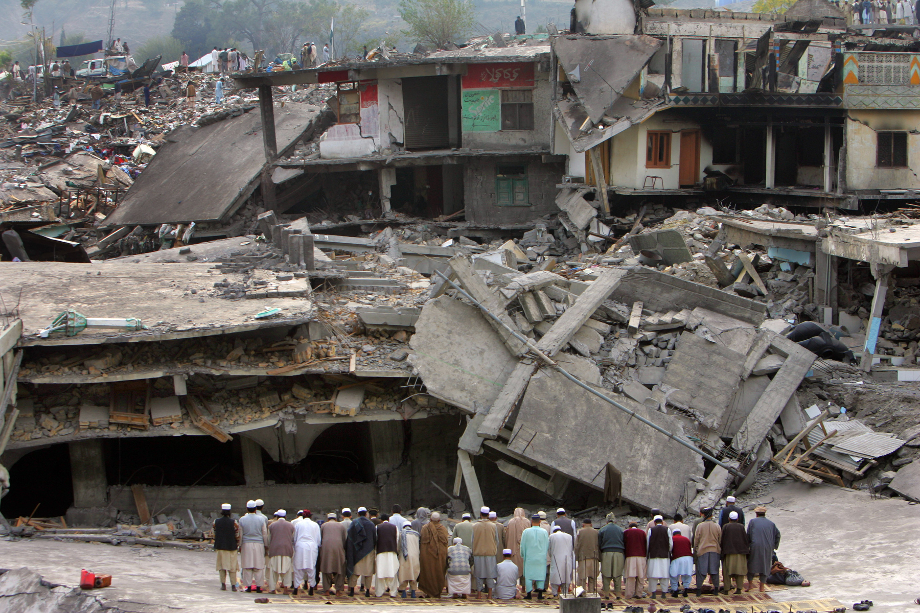 BALAKOT, PAKISTAN- Men pray in front of a destroyed mosque. A devastating earthquake measuring 7.6 on the Richter scale hit northern Pakistan and neighboring India leaving up to 3 million people homeless, killing almost 80,000. Rescue efforts were complicated by the remote mountainous landscape and the vast areas effected leaving the victims in desperate situations. In some areas,  injured were trapped for days with little food and no shelter as roads were blocked by landslides. Aid agencies could barely grasp the enormity of this natural disaster, the worst in Pakistan\'s history.