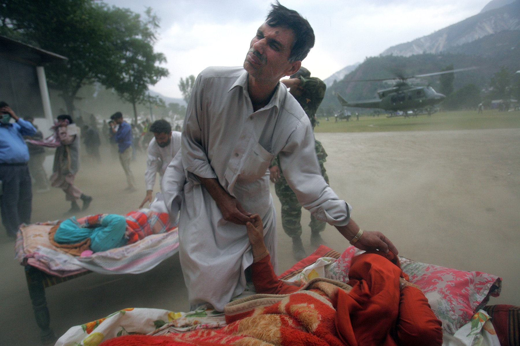 MUZAFFARABAD, PAKISTAN-OCTOBER 11:  Earthquake victims wait to get emergency first aid in a makeshift trauma center as a helicopter blows dust and high winds where many survivors from  Muzaffarabad and neighboring villages where taken.(photo by Paula Bronstein for Time magazine /Getty Images)