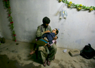 BALAKOT, PAKISTAN: A father holds his daughter  awaiting medical treatment at a makeshift trauma facility where earthquake survivors were brought in by helicopter from remote villages.  A devastating earthquake measuring 7.6 on the Richter scale hit northern Pakistan and neighboring India in early October leaving up to 3 million people homeless in Pakistan, killing almost 80,000 in Pakistan and another 1,400 in Indian-Kashmir. Rescue efforts were complicated by the remote mountainous landscape and the vast areas effected leaving the people in desperate situations. The injured were trapped for days with little food and no shelter as roads were blocked by landslides until helicopters were able to rescue the victims. Aid agencies could barely grasp the enormity of the natural disaster, the worst in Pakistan's history.