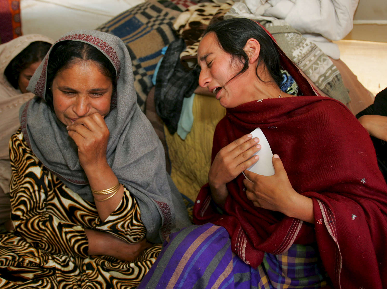 MUZAFFARABAD, PAKISTAN-OCTOBER 22:Naseem (L) and Nazmeen Akther (R) weep as they loook at photos of their children killed in the earthquake inside their tent in Muzaffarabad, Pakistan controlled Kashmir October 22,2005. the mothers joined relatives who visited them today to mourn their loss together. The current death toll is now believed to be over 50,000 from the South Asian earthquake that happened 2 weeks ago. Over 3 million people are without proper shelter and aid organizations including the U.N are warning that thousands could die in remote mountainous regions as Winter approaches. Atleast 1,400 died in Indian-Kashmir. (photo by Paula Bronstein /Getty Images)