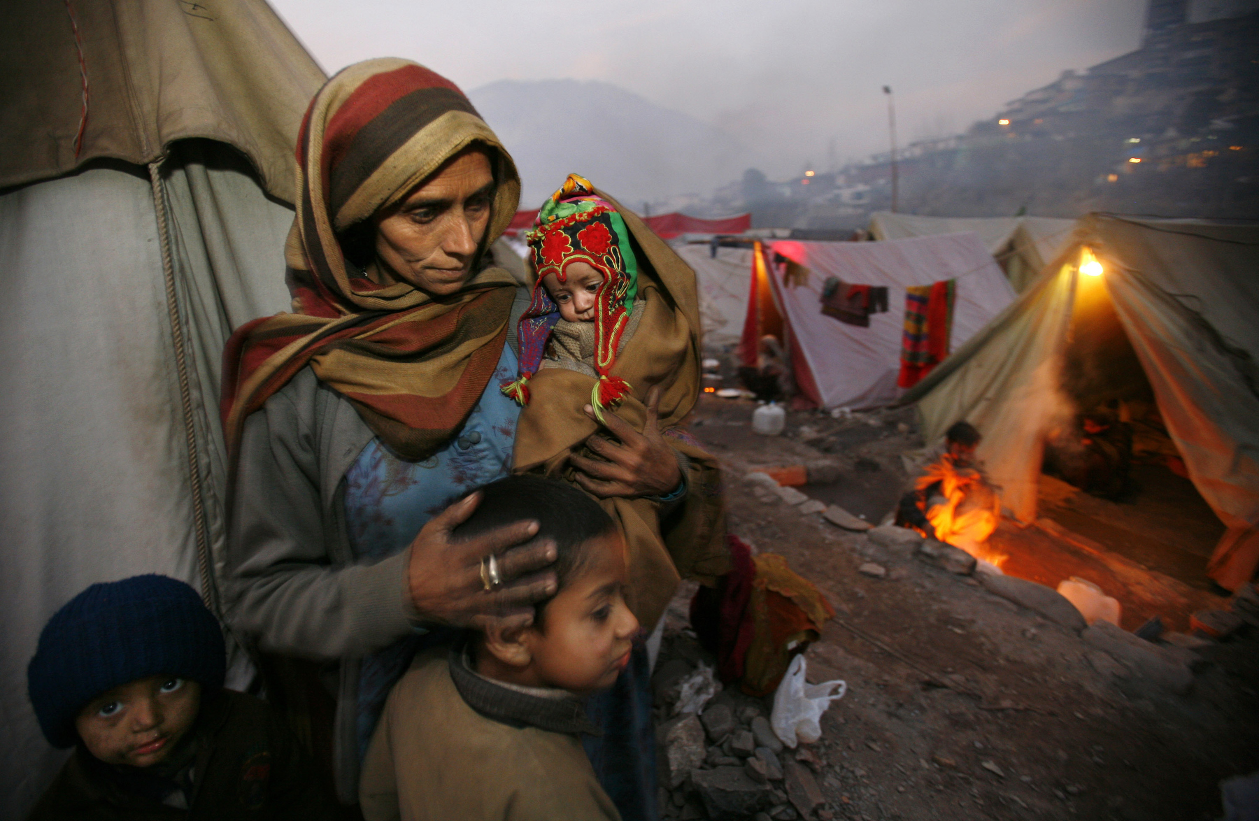 MUZAFFARABAD, PAKISTAN-DECEMBER 16: Nasim Jan holds her daughter Mehnaz, 2 months old with Farooq and Abdullah as try and keep warm residing at a tented camp in Muzaffarabad, December 16, 2005. The camp has over 700 tents housing 3,336 earthquake victims who have moved from various area villages for the winter months.  Lack of snow is giving the quake survivors a break but they are still struggling in over crowded tented camps while fighting the cold weather with a lack of shelter.  (photo by Paula Bronstein /Getty Images)