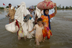 CHOKE GHODAR, PAKISTAN-AUG 27: Flood victims make their way along on a major flooded road as the water level goes down in the Punjab region allowing some to head home August 27, 2010 in Choke Ghodar, Pakistan. The country\'s agricultural heartland has been devastated as rice, corn and wheat crops have been destroyed by the floods, government officials claim as many as 20 million people have been effected by the flooding. Pakistan is suffering from the worst flooding in 80 years as aid organizations and the government struggle four weeks on with the wide spread scale of the disaster which has killed over 1,600 people and injured 2,000. The relief effort had improved in Sindh province but is still being hampered by logistical problems, including the ability to reach many of the victims. The U.N has described the disaster as unprecedented with over a third of the country under water. It has now received more than half of the $460 million appeal it issued last week to pay for humanitarian operations over the next three months. The Taliban has hinted that it may launch attacks against foreign aid workers calling their presence \{quote}unacceptable\{quote}. (Photo by Paula Bronstein/ Getty Images)