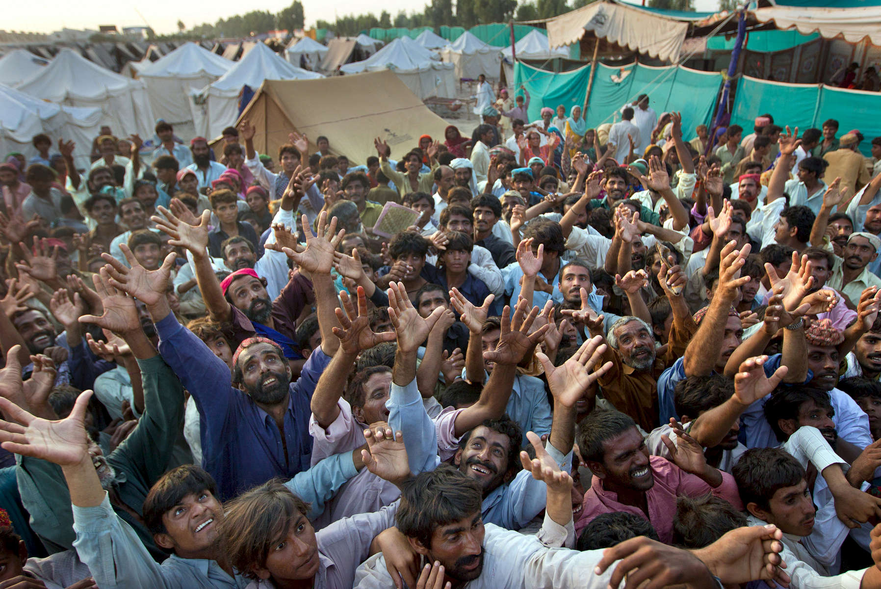 SUKKUR, PAKISTAN-AUG 19: Desperate flood victims scramble for some aid given out by the Pakistan military at a tented camp August 19, 2010 in Sukkur , Pakistan. The country\'s agricultural heartland has been devastated as rice, corn and wheat crops have been destroyed by the floods, government officials claim as many as 20 million people have been effected by the flooding with 15 million seriously effected. Pakistan is suffering from the worst flooding in 80 years as the army and aid organizations continue to struggle three weeks on with the wide spread scale of the disaster which has killed over 1,600 people and injured 2,000. The relief effort is being hampered by logistical problems, including the ability to reach many of the victims.  The U.N has described the disaster as unprecedented with over a third of the country under water. It has now received more than half of the $460 million appeal it issued last week to pay for humanitarian operations over the next three months. (Photo by Paula Bronstein/ Getty Images)