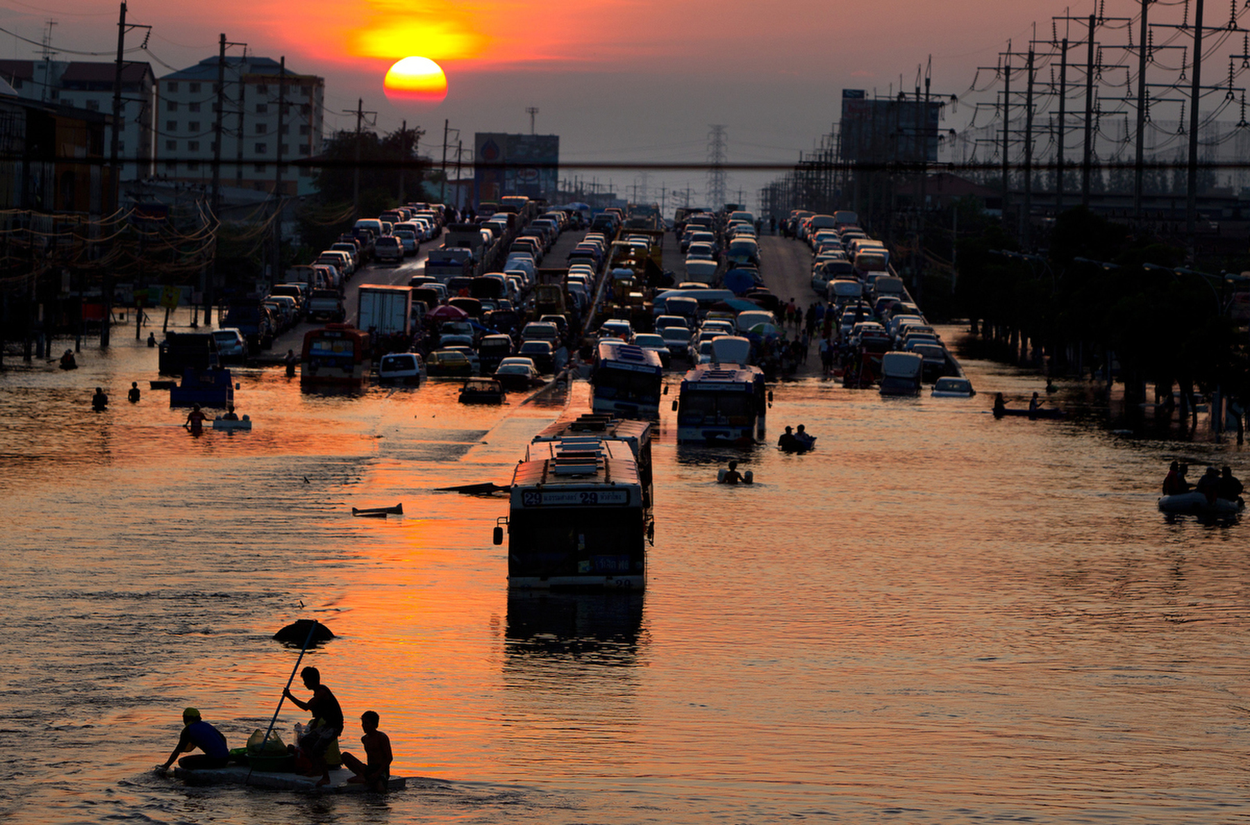 RANGSIT,THAILAND - OCTOBER 24rd: Flood victims make their way through the high waters as the sunsets along the flooded streets in Rangsit on the outskirts of Bangkok October 24, 2011 in Bangkok, Thailand. Hundreds of factories closed in the central Thai province of Ayutthaya and Nonthaburi as the waters come closer to threaten Bangkok as well. Around 350 people have died in flood-related incidents since late July according to the Department of Disaster Prevention and Mitigation. Thailand is experiencing the worst flooding in 50 years with damages running as high as $6 billion which could increase of the floods swamp Bangkok.(Photo by Paula Bronstein /Getty Images)
