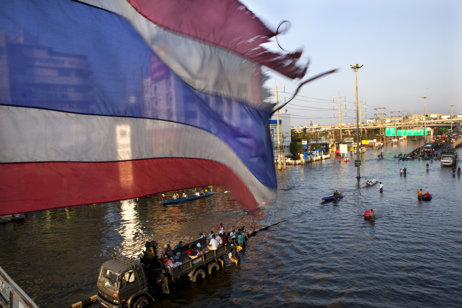 BANGKOK,THAILAND - NOVEMBER 16 :  An old tattered Thai flag blows over a bridge in the flooded district of Rangsit November 16, 2011 in Bangkok, Thailand. U.S Secretary of State Hillary Clinton Clinton came to Thailand today to offer support and significant US help in confronting Thailand\'s massive flooding. Over seven major industrial parks in Bangkok and, thousands of factories have been closed in the central Thai province of Ayutthaya and Nonthaburi with millions of tons of rice damaged. Across the country, the flooding which is now in its third month has affected 25 of Thailand\'s 64 provinces. Thailand is experiencing the worst flooding in over 50 years which has affected more than nine million people. The death toll stands at 562 people. (Photo by Paula Bronstein /Getty Images)