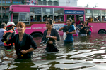BANGKOK,THAILAND - NOVEMBER 7 :  Commuters get off a city bus into waist deep water in the Bang Kae district southwest of the capitol city November 7, 2011 in Bangkok, Thailand. Over seven major industrial parks in Bangkok and, thousands of factories have been closed in the central Thai province of Ayutthaya and Nonthaburi with millions of tons of rice damaged. Across the country, the flooding which is now in its third month has affected 25 of Thailand\'s 64 provinces. Thailand is experiencing the worst flooding in over 50 years which has affected more than nine million people. Over 400 people have died in flood-related incidents since late July according to the Department of Disaster Prevention and Mitigation.(Photo by Paula Bronstein /Getty Images)