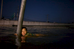 RANGSIT,THAILAND - OCTOBER 24rd: A woman hangs onto a street sign in chest deep water along the flooded streets in Rangsit on the outskirts of Bangkok October 24, 2011 in Bangkok, Thailand. Hundreds of factories closed in the central Thai province of Ayutthaya and Nonthaburi as the waters come closer to threaten Bangkok as well. Around 350 people have died in flood-related incidents since late July according to the Department of Disaster Prevention and Mitigation. Thailand is experiencing the worst flooding in 50 years with damages running as high as $6 billion which could increase of the floods swamp Bangkok.(Photo by Paula Bronstein /Getty Images)