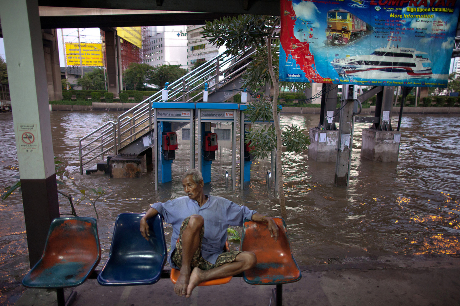 BANGKOK,THAILAND - NOVEMBER 2 : A Thai man sits at a flooded train station in the Laksi area  November 2, 2011 in Bangkok, Thailand. Thousands of flood victims have been forced to take shelter at crowded evacuation centers around the capitol city. Hundreds of factories have been closed in the central Thai province of Ayutthaya and Nonthaburi and millions of tons of rice has been damaged. Thailand is experiencing the worst flooding in over 50 years which has affected more than nine million people. Over 400 people have died in flood-related incidents since late July according to the Department of Disaster Prevention and Mitigation.(Photo by Paula Bronstein /Getty Images)