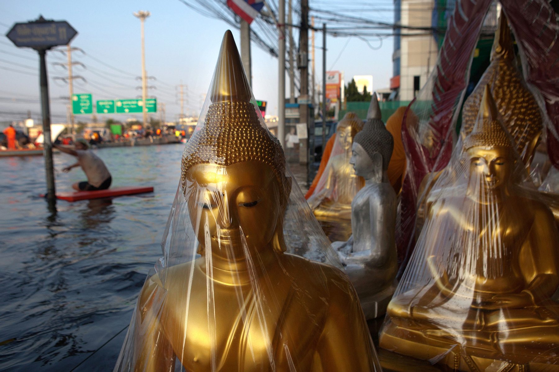 RANGSIT,THAILAND - OCTOBER 24rd: A flooded shop selling buddha statues is seen along the flooded streets in Rangsit on the outskirts of Bangkok October 24, 2011 in Bangkok, Thailand. Hundreds of factories closed in the central Thai province of Ayutthaya and Nonthaburi as the waters come closer to threaten Bangkok as well. Around 350 people have died in flood-related incidents since late July according to the Department of Disaster Prevention and Mitigation. Thailand is experiencing the worst flooding in 50 years with damages running as high as $6 billion which could increase of the floods swamp Bangkok.(Photo by Paula Bronstein /Getty Images)