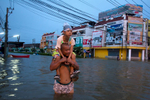 AYUTTHAYA,THAILAND - OCTOBER 10TH:  A Thai man holds his daughter a he wades through the flooded streets October 10, 2011 in Ayutthaya, Thailand Around 200 factories closed in the central Thai province of Ayutthaya because of flooding, which is posing a threat to Bangkok as well. Over 260 people have died in flood-related incidents since late July according to the Department of Disaster Prevention and Mitigation. Some areas of the country are experiencing the worst flooding in 50 years, mainly in the centre, north and northeast.(Photo by Paula Bronstein /Getty Images)