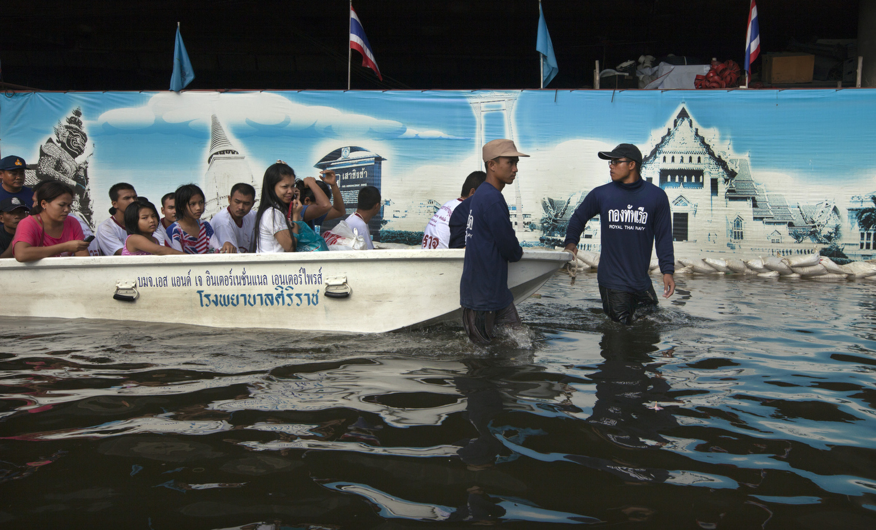 BANGKOK,THAILAND - OCTOBER 29: Thai military pull a boat full of people past a mural in a flooded neighborhood near the Chayo Praya river as rising waters threaten parts of the capitol city October 29, 2011 in Bangkok, Thailand. Hundreds of factories have been closed in the central Thai province of Ayutthaya and Nonthaburi. Thailand is experiencing the worst flooding in over 50 years which has affected more than nine million people. Over 400 people have died in flood-related incidents since late July according to the Department of Disaster Prevention and Mitigation.(Photo by Paula Bronstein /Getty Images)