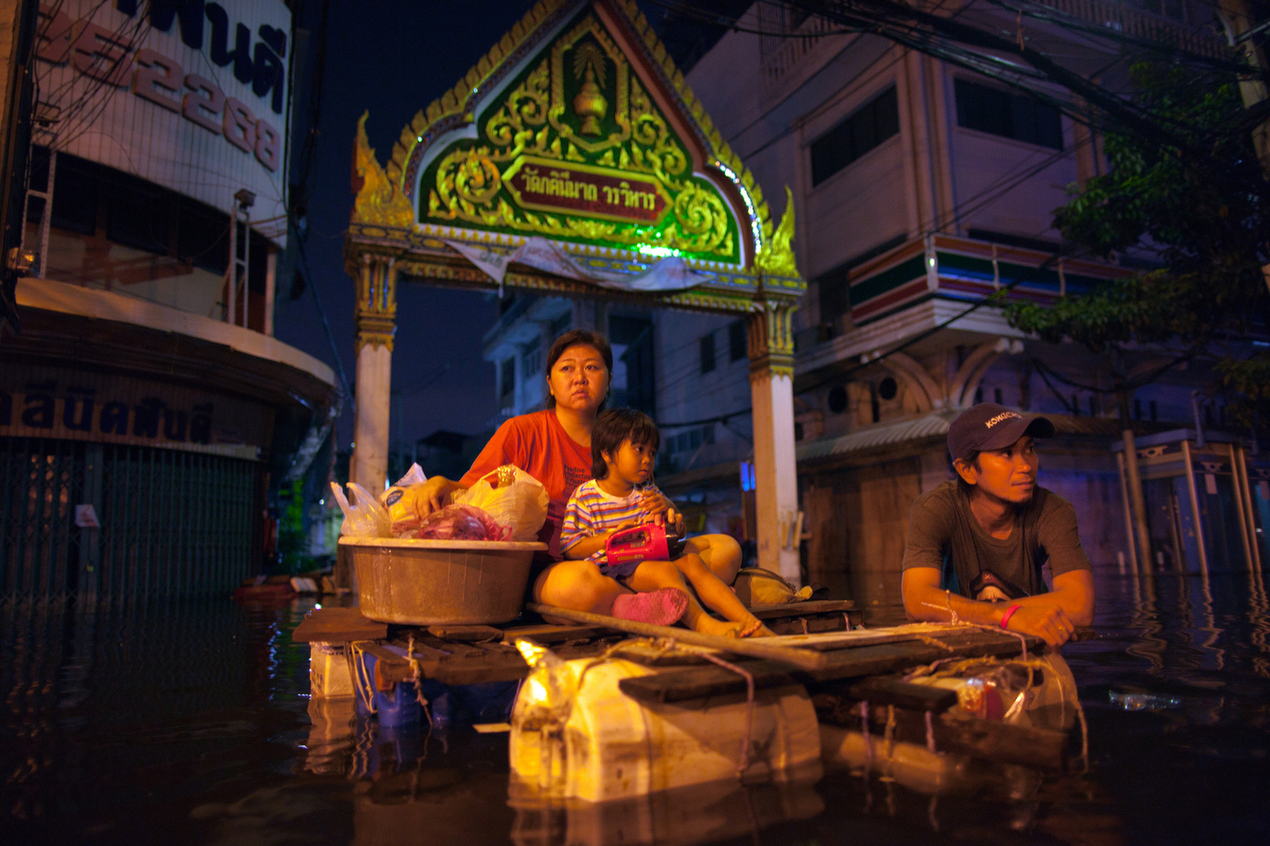 BANGKOK,THAILAND - OCTOBER 31:  Tassaporn holds her son Poonawat,3, on a makeshift raft as they wait for more supplies to bring home in the Thonburi area October 31, 2011 in Bangkok, Thailand. Thousands of flood victims have been forced to take shelter at crowded evacuation centers around the capitol city. Hundreds of factories have been closed in the central Thai province of Ayutthaya and Nonthaburi. Thailand is experiencing the worst flooding in over 50 years which has affected more than nine million people. Over 400 people have died in flood-related incidents since late July according to the Department of Disaster Prevention and Mitigation.(Photo by Paula Bronstein /Getty Images)