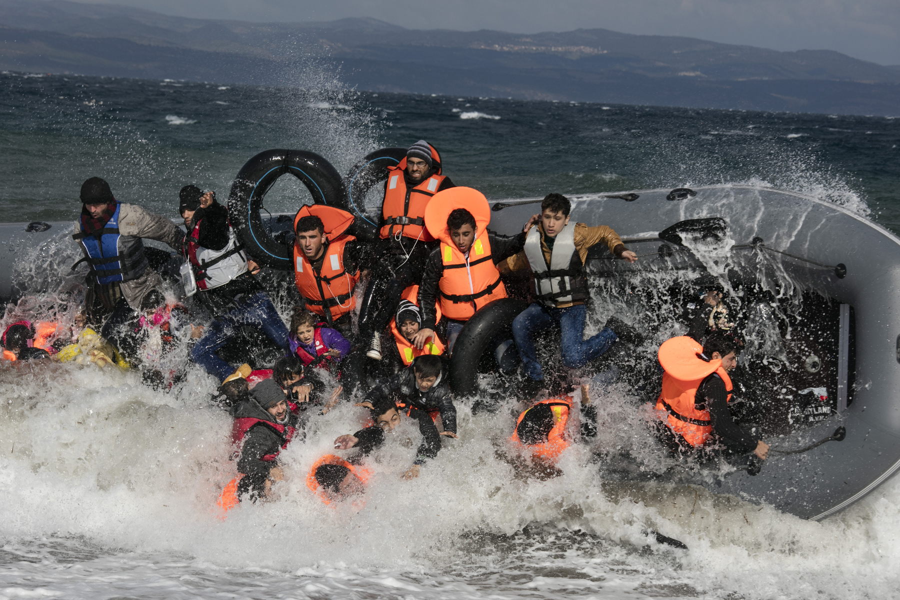 LESBOS, GREECE - OCTOBER 31: Refugees arriving to the island of Lesbos fall out of a boat as it capsizes landing in rough seas coming from Turkey on October 31, 2015 in Lesbos, Greece. Dozens of rafts and boats are still making the journey daily via the Aegean Sea, over 590,000 people have crossed into the gateway of Europe. Nearly all of those are from the war zones of Syria, Iraq and Afghanistan. (Photo by Paula Bronstein)