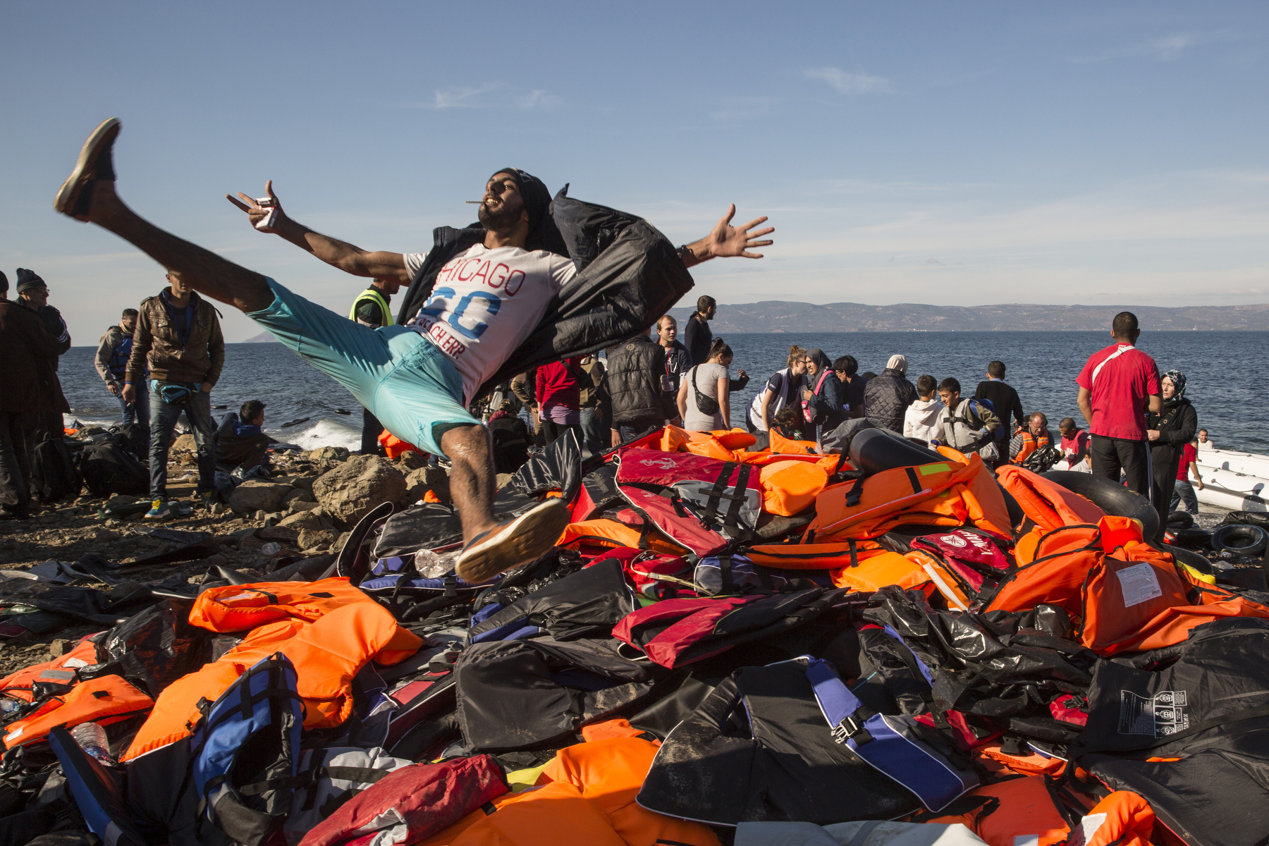 LESBOS, GREECE - OCTOBER 27: A Syrian refugee jumps for joy onto a pile of life jackets after arriving on an overcrowded raft to the island of Lesbos, Greece on October 27, 2015. Dozens of rafts and boats are still making the journey daily via the Aegean Sea, over 590,000 people have crossed into the gateway of Europe. Nearly all of those are from the war zones of Syria, Iraq and Afghanistan. (Photo by Paula Bronstein)
