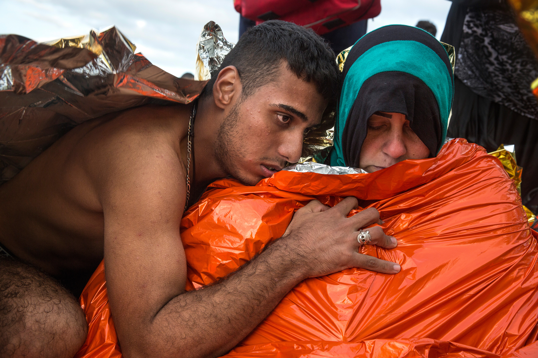 LESBOS, GREECE - OCTOBER 27: A Syrian man hugs his wife who is getting medical attention suffering from hypothermia after arriving on a raft to the island of Lesbos, Greece on October 27, 2015. Dozens of rafts and boats are still making the journey daily via the Aegean Sea, over 590,000 people have crossed into the gateway of Europe. Nearly all of those are from the war zones of Syria, Iraq and Afghanistan. (Photo by Paula Bronstein)