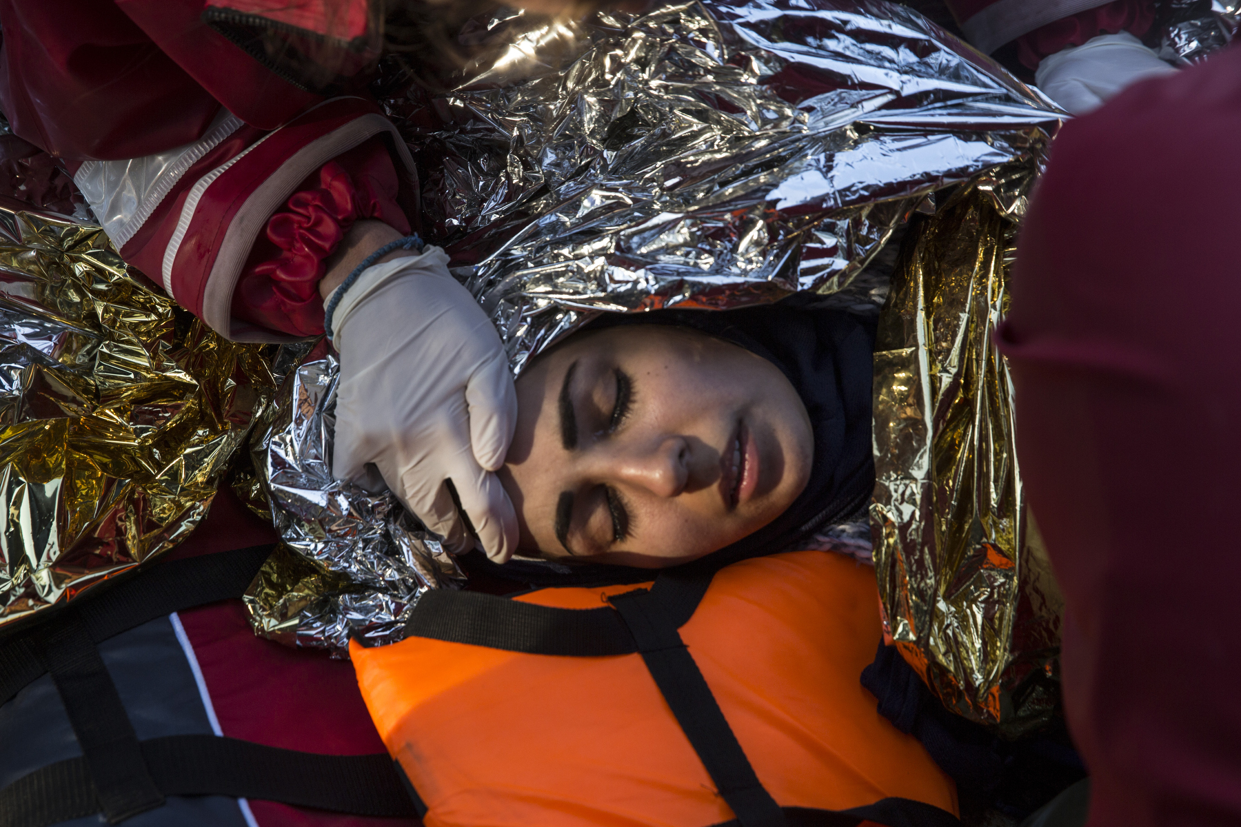LESBOS, GREECE - OCTOBER 26: Volunteers with the Greek ( Hellenic) Red Cross tend to a Syrian woman  who was suffering from hypothermia after a boat that just landed. Colder weather and rough seas continue to cause deaths at sea as thousands travel in overcrowded small rafts. According to the IOM, an estimated 100,000 people landed in Greece, an average of almost 4,500 per day in late October and November. Nearly all of those entering Greece on a boat from Turkey are from the war zones of Syria, Iraq and Afghanistan. (Photo by Paula Bronstein)