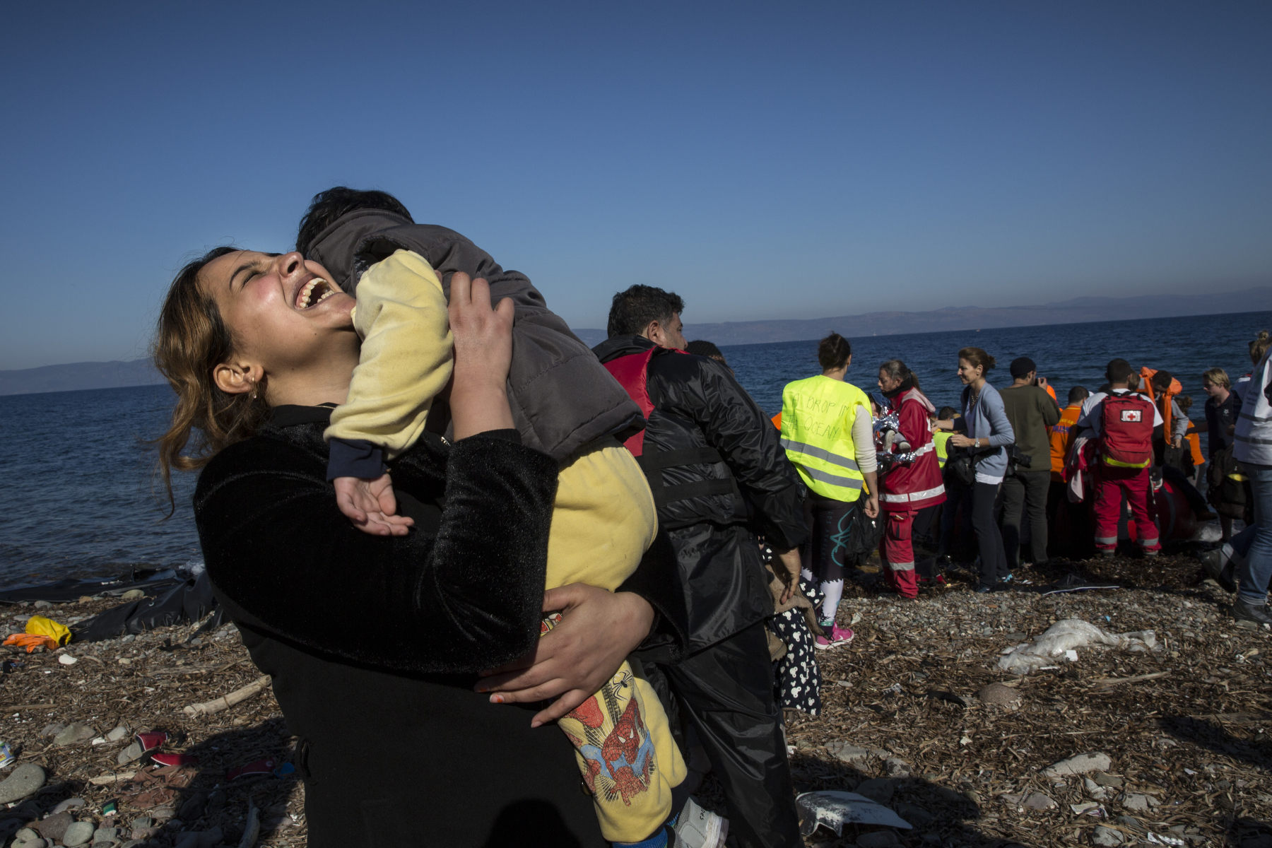 LESBOS, GREECE - NOVEMBER 12: A Syrian refugee rejoices after arriving on an overcrowded raft to the island of Lesbos, Greece on November 12, 2015. Dozens of rafts and boats are still making the journey daily via the Aegean Sea, over 590,000 people have crossed into the gateway of Europe. Nearly all of those are from the war zones of Syria, Iraq and Afghanistan. (Photo by Paula Bronstein)
