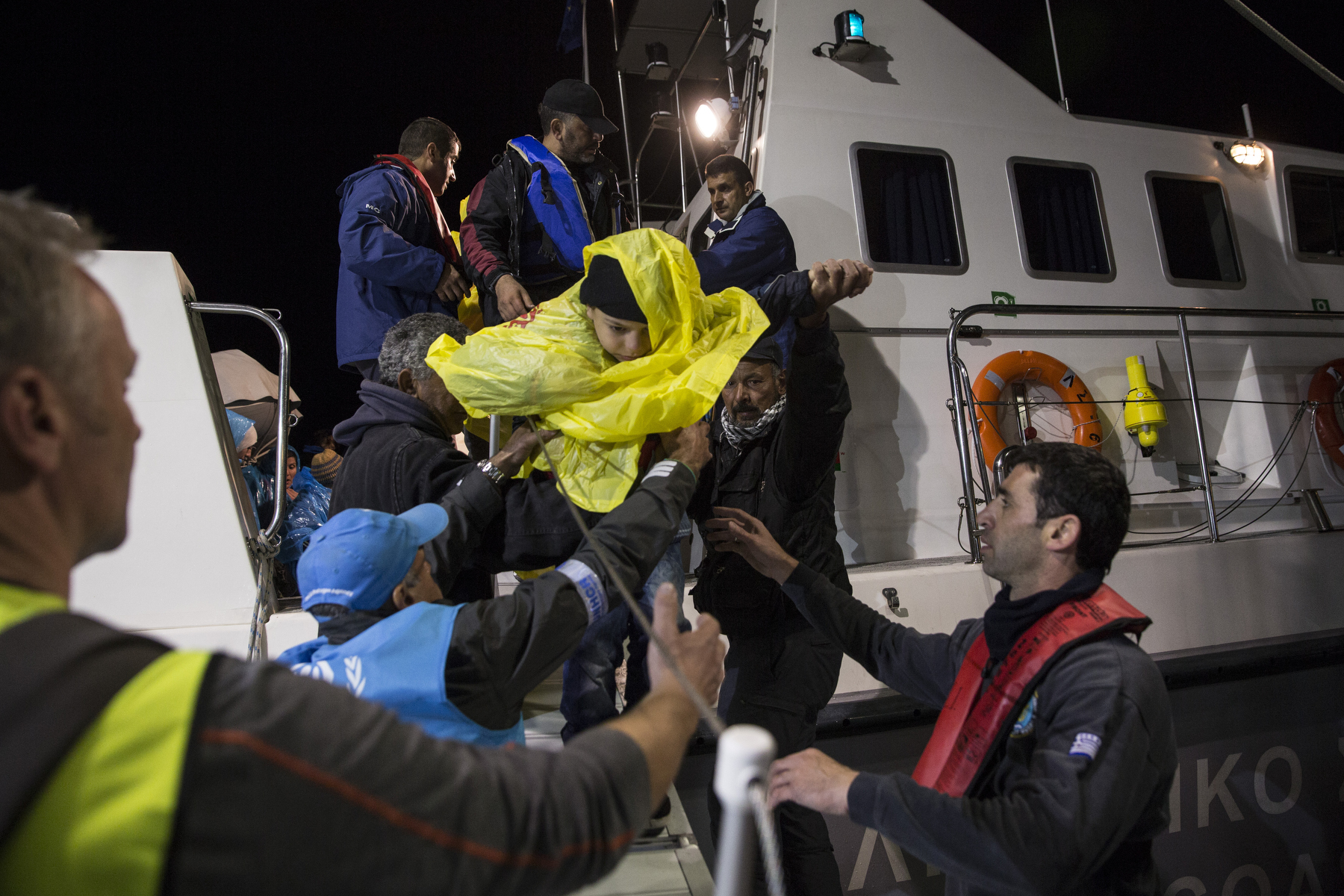 LESBOS, GREECE - OCTOBER 29: A boy is rescued by Greek Coast guard after a large wooden boat capsized. Colder weather and rough seas continue to cause deaths at sea as thousands travel in overcrowded small rafts. According to the IOM, an estimated 100,000 people landed in Greece, an average of almost 4,500 per day in late October and November. Nearly all of those entering Greece on a boat from Turkey are from the war zones of Syria, Iraq and Afghanistan. (Photo by Paula Bronstein)