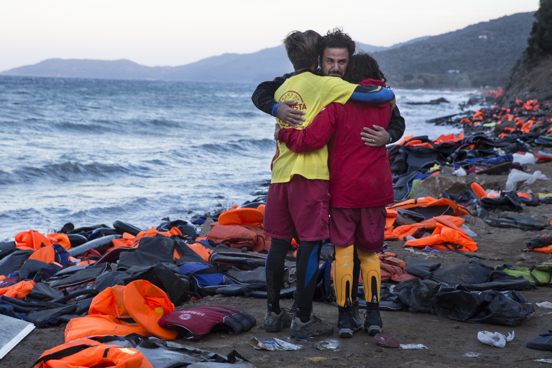 LESBOS, GREECE - OCTOBER 30: Israeli Doctor Essam Daod ( center) cries getting comforted by Proactiva lifeguards from Spainon Lesbos, Greece on October 30, 2015. The emergency team made a huge effort trying to save the refugee who later died after being rescued from the open waters of the Aegean sea. The man died despite the efforts of the lifeguards and medical personnel to revive him. Dozens of rafts and boats are still making the journey daily over 590,000 people have crossed into the gateway of Europe. Nearly all of those are from the war zones of Syria, Iraq and Afghanistan. (Photo by Paula Bronstein)