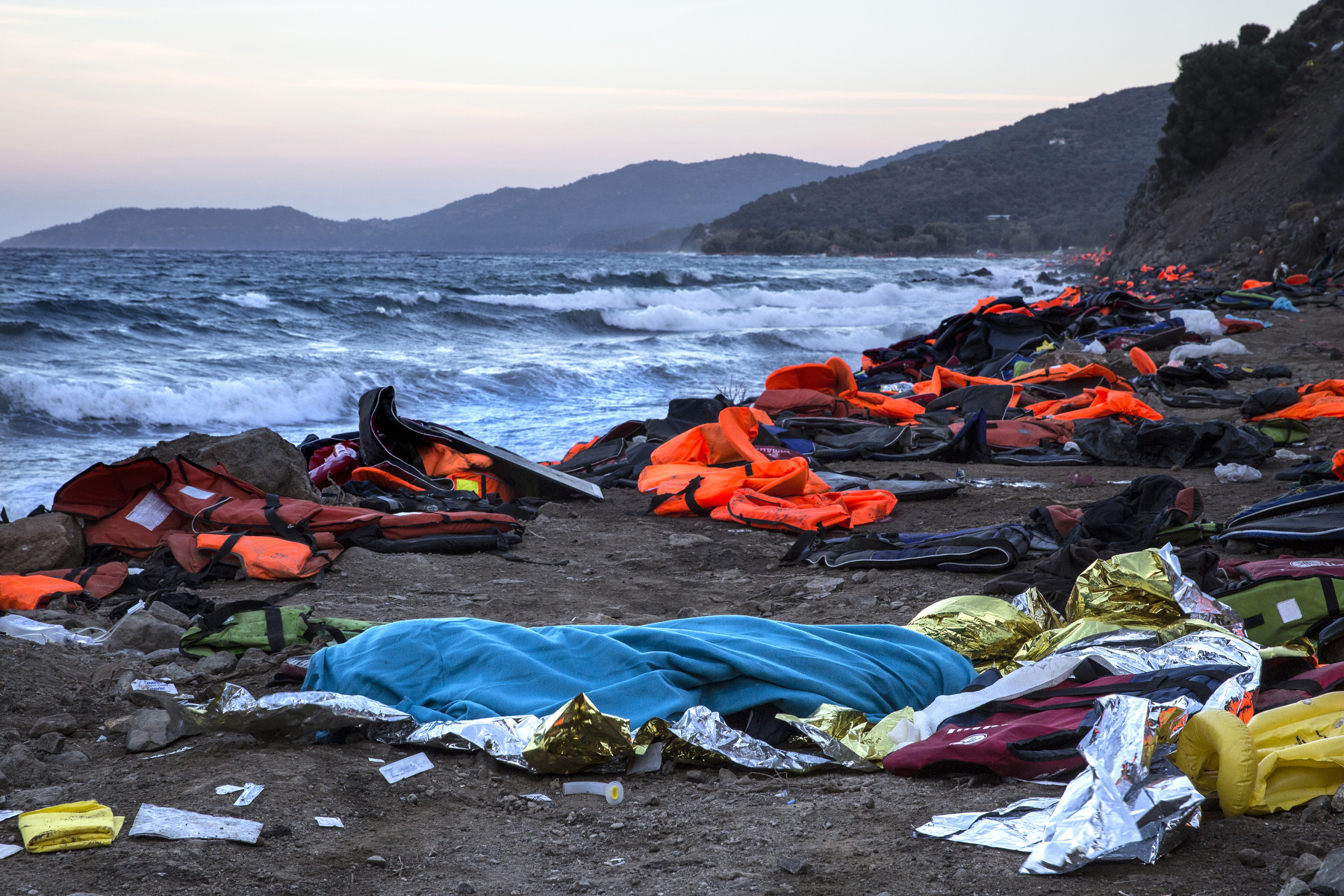 LESBOS, GREECE - OCTOBER 30: The body of a man is seen covered by a blanket after being rescued from the open waters of the Aegean sea on the island of Lesbos, Greece on October 30, 2015. The man died despite the efforts of the lifeguards and medical personnel to revive him. Dozens of rafts and boats are still making the journey daily over 590,000 people have crossed into the gateway of Europe. Nearly all of those are from the war zones of Syria, Iraq and Afghanistan. (Photo by Paula Bronstein)