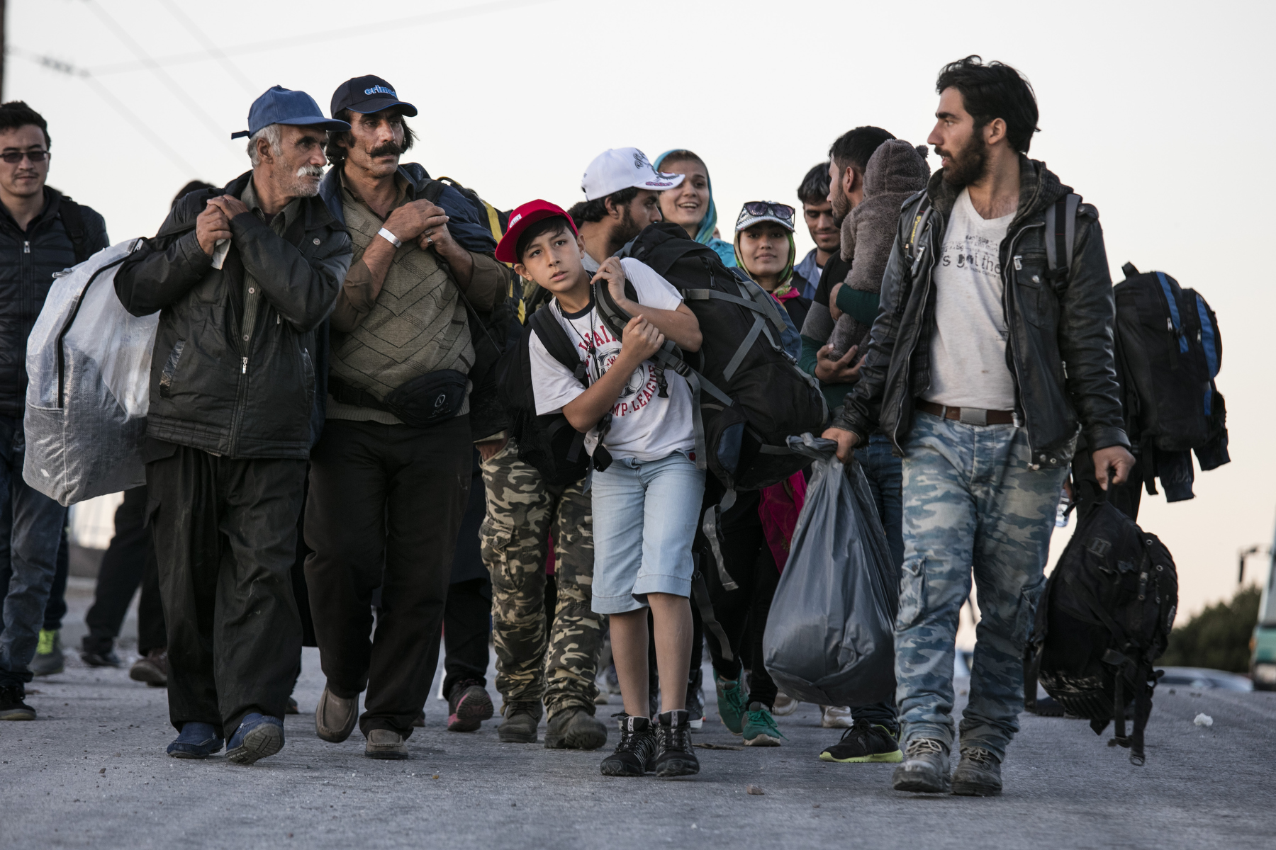 LESBOS, GREECE - NOVEMBER 3: Refugees walk to a transitional camp to spend the night. Colder weather and rough seas continue to cause deaths at sea as thousands travel in overcrowded small rafts. According to the IOM, an estimated 100,000 people landed in Greece, an average of almost 4,500 per day in late October and November. Nearly all of those entering Greece on a boat from Turkey are from the war zones of Syria, Iraq and Afghanistan. (Photo by Paula Bronstein)