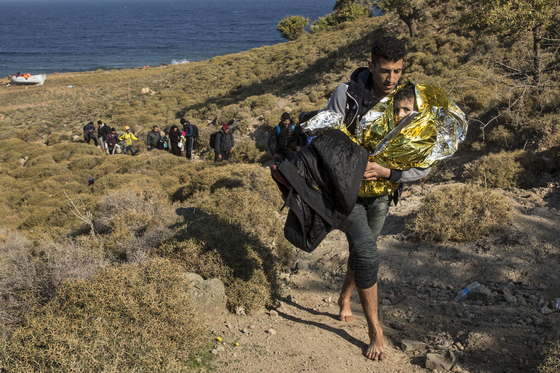LESBOS, GREECE - NOVEMBER 15: A man carries his child walking barefoot up a hill to a main road after arriving by boat to Lesbos. According to the IOM, an estimated 100,000 people landed in Greece, an average of almost 4,500 per day in late October and November. Nearly all of those entering Greece on a boat from Turkey are from the war zones of Syria, Iraq and Afghanistan. (Photo by Paula Bronstein)