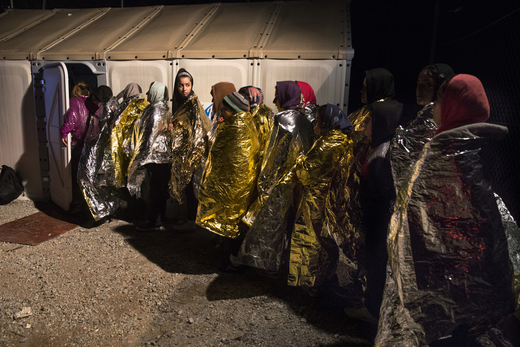 LESBOS, GREECE - OCTOBER 25: Women keep warm wrapped in emergency blankets while standing in line to change out of their wet clothes at a transitional camp. Colder weather and rough seas continue to cause deaths at sea as thousands travel in overcrowded small rafts. According to the IOM, an estimated 100,000 people landed in Greece, an average of almost 4,500 per day in late October and November. Nearly all of those entering Greece on a boat from Turkey are from the war zones of Syria, Iraq and Afghanistan. (Photo by Paula Bronstein)