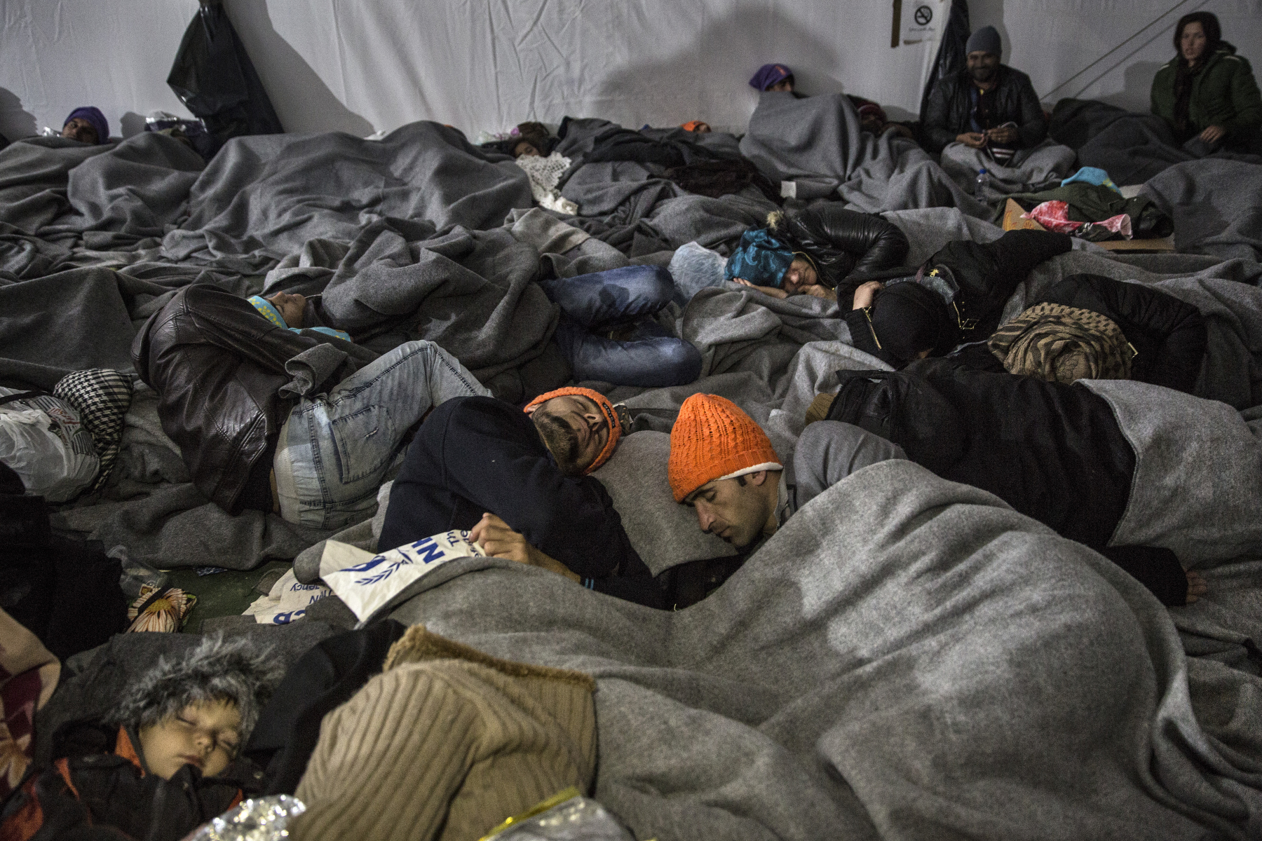 LESBOS, GREECE - OCTOBER 26: Refugees piled on top of each other sleep inside a large tent a transitional camp Lesbos, on October 30, 2015. to the IOM, an estimated 100,000 people landed in Greece, an average of almost 4,500 per day in late October and November. Nearly all of those entering Greece on a boat from Turkey are from the war zones of Syria, Iraq and Afghanistan. (Photo by Paula Bronstein)