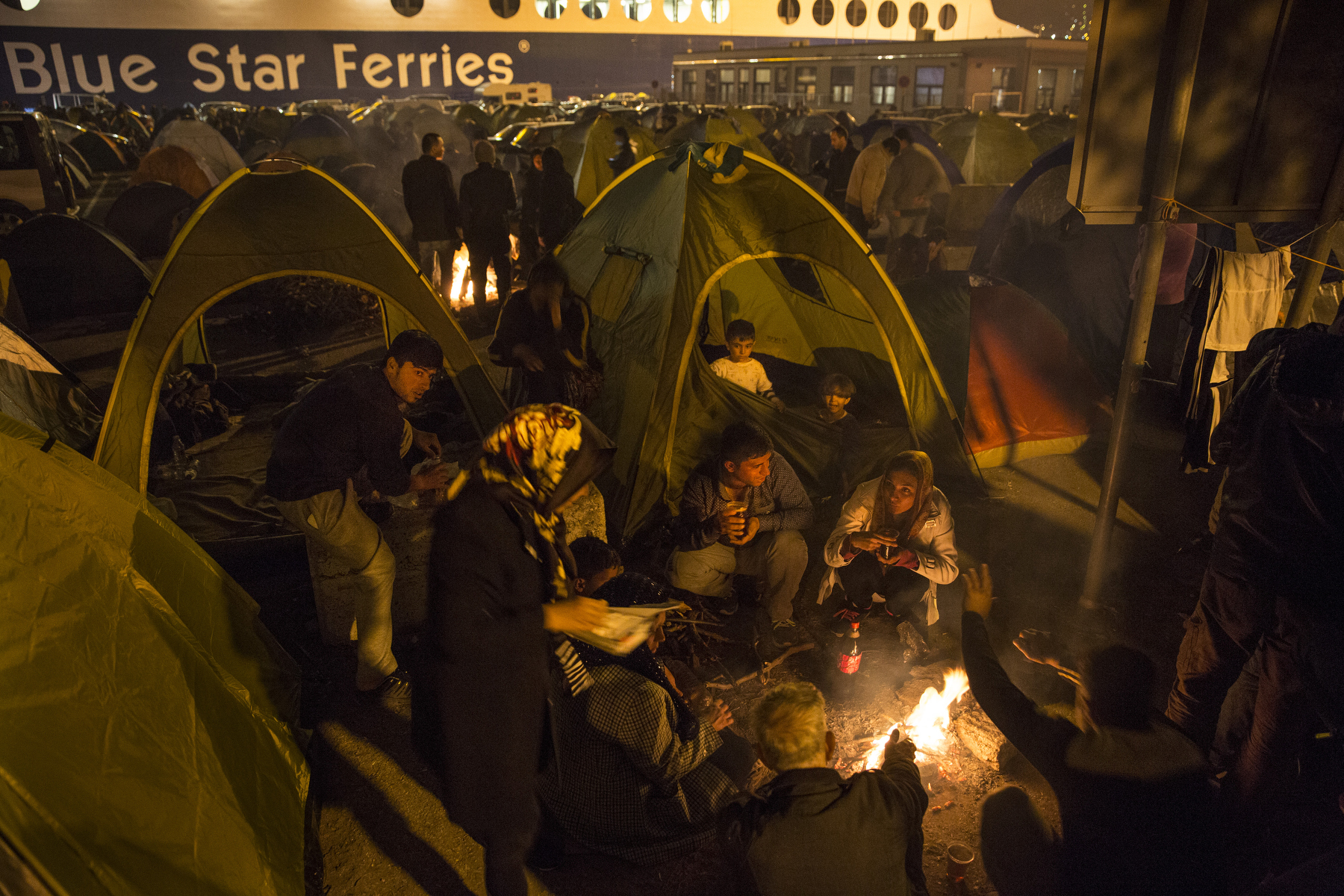 LESBOS, GREECE - NOVEMBER 5: Refugees take over the ferry terminal turning it into a campground as they wait for days to board the ferry to Athens on Lesbos, Greece on November 5, 2015. Dozens of rafts and boats are still making the journey daily over 590,000 people have crossed into the gateway of Europe. Nearly all of those are from the war zones of Syria, Iraq and Afghanistan. (Photo by Paula Bronstein)