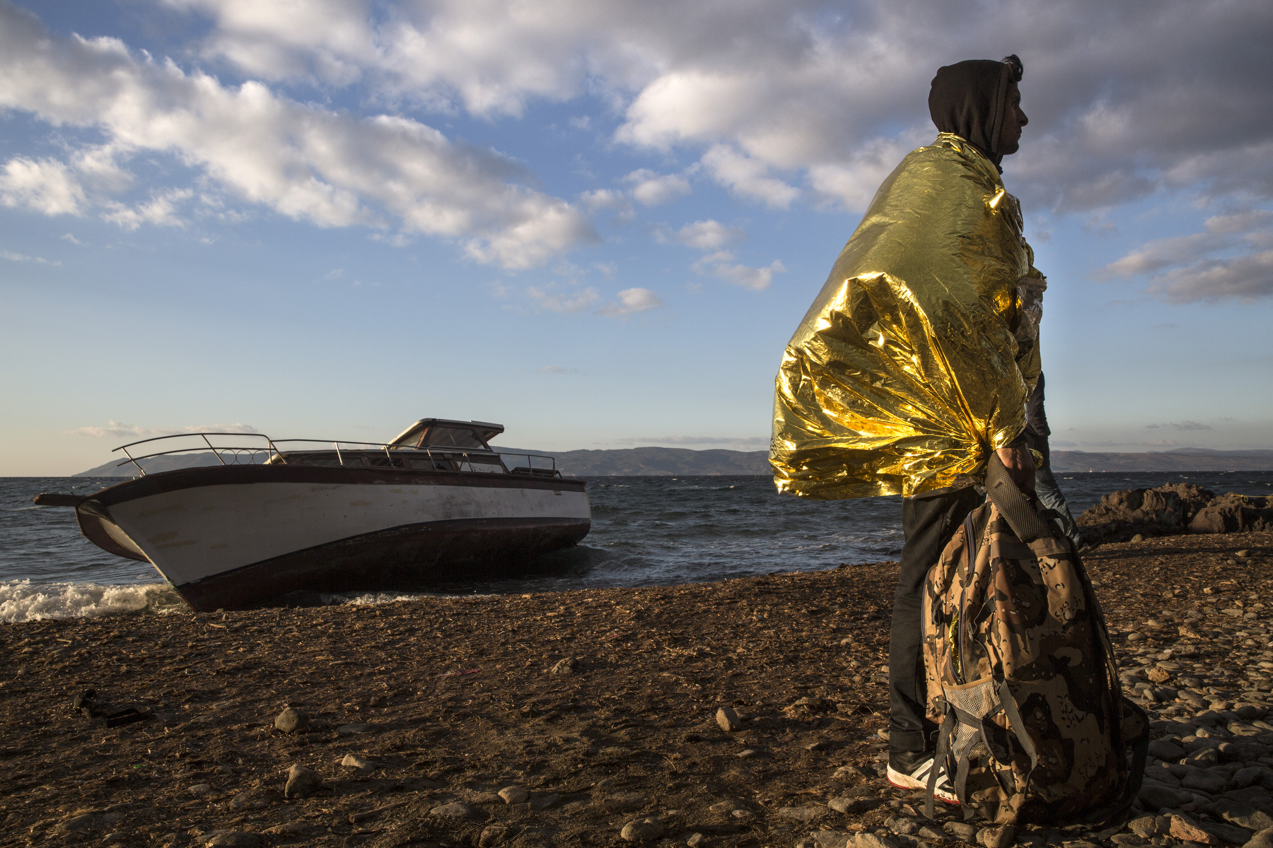 LESBOS, GREECE - OCTOBER 25: A refugee wrapped in an emergency blanket stands on Iftalou beach on Lesbos next to a refugee shipwreck. Colder weather and rough seas continue to cause deaths at sea as thousands travel in overcrowded small rafts. According to the IOM, an estimated 100,000 people landed in Greece, an average of almost 4,500 per day in late October and November. Nearly all of those entering Greece on a boat from Turkey are from the war zones of Syria, Iraq and Afghanistan. (Photo by Paula Bronstein)