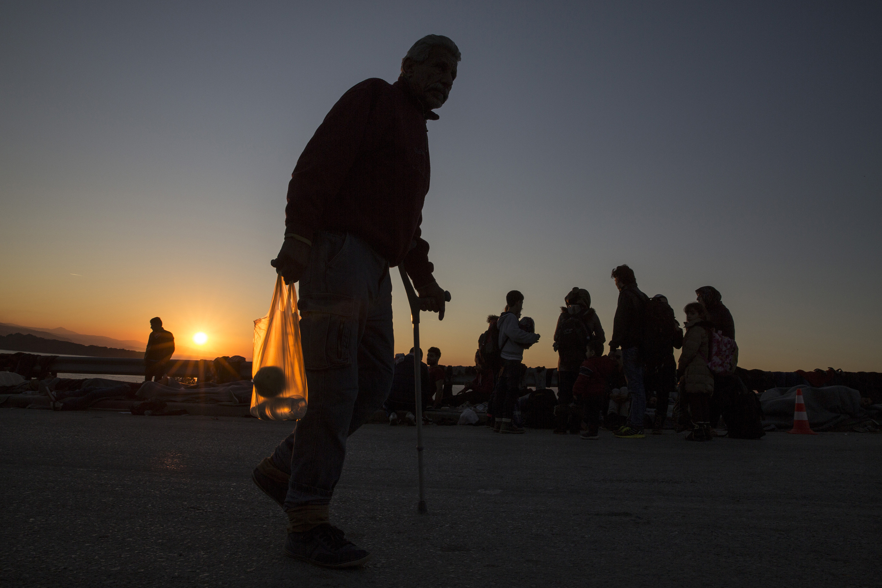 LESBOS, GREECE - NOVEMBER 4 :  A handicapped Syrian refugee man carries some food as the sunsets at Oxy transitional camp  on Lesbos, Greece on November 4 , 2015.  Dozens of rafts and boats are still making the journey daily over 590,000 people have crossed into the gateway of Europe. Nearly all of those are from the war zones of Syria, Iraq and Afghanistan. (Photo by Paula Bronstein)