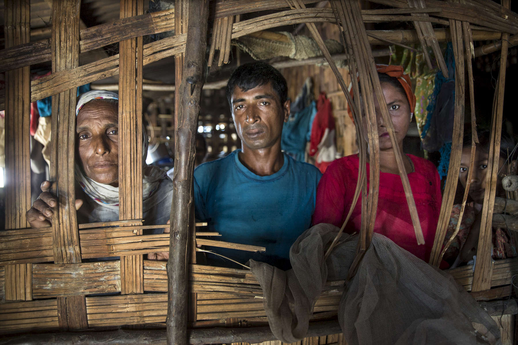 MAYEBON - NOV 8: Albella (left) Abdul Hamid,40(center) and Moria Katu (right) look through the window of a thatched hut at the Mayebon IDP camp where registration has taken place forcing the residents of the camp to list themselves as Bengali not Rohingya. The new policy is called the Rakhine Action Plan. (Paula Bronstein for The Washington Post)