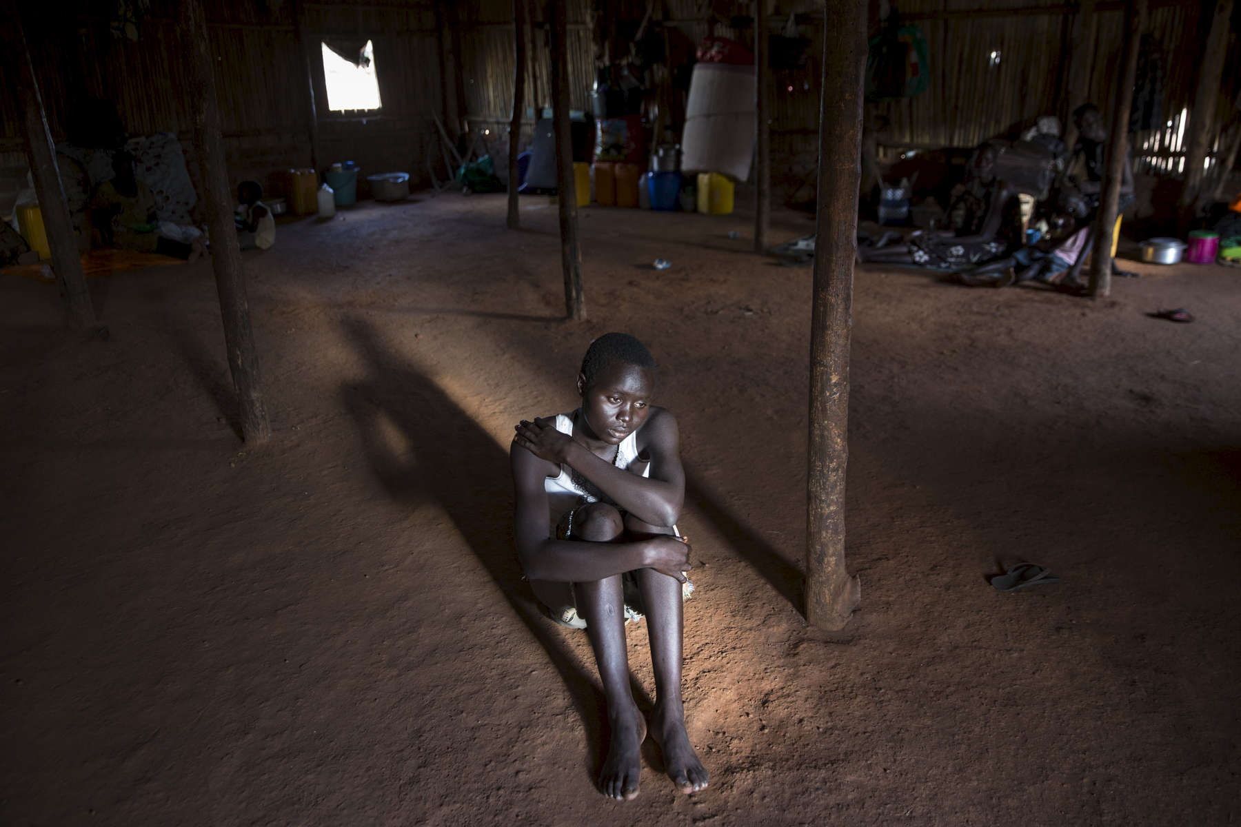 ADJUMANI DISTRICT-UGANDA: At the Nyumanzi transit camp Esther Ababiku, 16, is one of the many girls who lost her parents, forced to flee on her own unaccompanied and vulnerable to sexual attacks. She lives with other teens who are also orphans of the war. The Onward Struggle:  A refugee crisis in Uganda deepens as South Sudanese Refugees are forced to leave their country behind. The outbreak of violence in the capital Juba last July created a humanitarian crisis in northern Uganda as thousands of South Sudanese sought refugee there. The country is hosting the lion's share of South Sudanese refugees, with 373,626, more than a third of them arriving since early July.The fighting was a major setback to peace efforts in South Sudan, coming as the troubled new nation prepared to celebrate its fifth anniversary, amid a short lived peace deal between supporters of President Salva Kiir and former First Vice President Riek Machar. South Sudan now joins Syria, Afghanistan and Somalia as countries which have produced more than a million refugees. While some South Sudanese may attempt to head for Europe, the numbers within east Africa are comparable in scale to recent refugee flows to Europe from the Middle East, and their traumatic experiences due to war are often just as hellish. More than 85 percent of the refugees in this recent influx are women and children. Many children have lost one or both of their parents, some forced to become primary caregivers to siblings.With the large influx of refugees in July 2015, relief agencies had to implement stringent food rationing in the refugee settlements. Currently the international humanitarian organizations lack the necessary funds to meet the needs of the more than 200,000 refugees.