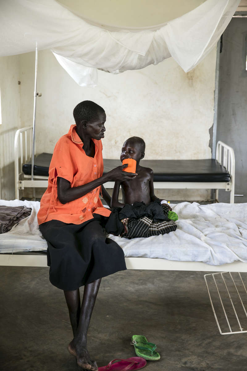 ADJUMANI DISTRICT-UGANDA: At the Nyumanzi health clinic a mother feeds her severely malnourished child. The Onward Struggle:  A refugee crisis in Uganda deepens as South Sudanese Refugees are forced to leave their country behind. The outbreak of violence in the capital Juba last July created a humanitarian crisis in northern Uganda as thousands of South Sudanese sought refugee there. The country is hosting the lion's share of South Sudanese refugees, with 373,626, more than a third of them arriving since early July.The fighting was a major setback to peace efforts in South Sudan, coming as the troubled new nation prepared to celebrate its fifth anniversary, amid a short lived peace deal between supporters of President Salva Kiir and former First Vice President Riek Machar. South Sudan now joins Syria, Afghanistan and Somalia as countries which have produced more than a million refugees. While some South Sudanese may attempt to head for Europe, the numbers within east Africa are comparable in scale to recent refugee flows to Europe from the Middle East, and their traumatic experiences due to war are often just as hellish. More than 85 percent of the refugees in this recent influx are women and children. Many children have lost one or both of their parents, some forced to become primary caregivers to siblings.With the large influx of refugees in July 2015, relief agencies had to implement stringent food rationing in the refugee settlements. Currently the international humanitarian organizations lack the necessary funds to meet the needs of the more than 200,000 refugees.
