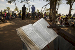 ADJUMANI DISTRICT-UGANDA:  During a Catholic Sunday prayer service held under the shade of a tree, refugees sit and pray as priests deliver their sermon.The Onward Struggle:  A refugee crisis in Uganda deepens as South Sudanese Refugees are forced to leave their country behind. The outbreak of violence in the capital Juba last July created a humanitarian crisis in northern Uganda as thousands of South Sudanese sought refugee there. The country is hosting the lion's share of South Sudanese refugees, with 373,626, more than a third of them arriving since early July.The fighting was a major setback to peace efforts in South Sudan, coming as the troubled new nation prepared to celebrate its fifth anniversary, amid a short lived peace deal between supporters of President Salva Kiir and former First Vice President Riek Machar. South Sudan now joins Syria, Afghanistan and Somalia as countries which have produced more than a million refugees. While some South Sudanese may attempt to head for Europe, the numbers within east Africa are comparable in scale to recent refugee flows to Europe from the Middle East, and their traumatic experiences due to war are often just as hellish. More than 85 percent of the refugees in this recent influx are women and children. Many children have lost one or both of their parents, some forced to become primary caregivers to siblings.With the large influx of refugees in July 2015, relief agencies had to implement stringent food rationing in the refugee settlements. Currently the international humanitarian organizations lack the necessary funds to meet the needs of the more than 200,000 refugees.