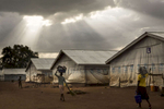 ADJUMANI DISTRICT-UGANDA: Nyumanzi transit camp: Refugees walk iafter a rainstorm. Hundreds of people are crammed into large tents, living there for months..The Onward Struggle:  A refugee crisis in Uganda deepens as South Sudanese Refugees are forced to leave their country behind. The outbreak of violence in the capital Juba last July created a humanitarian crisis in northern Uganda as thousands of South Sudanese sought refugee there. The country is hosting the lion's share of South Sudanese refugees, with 373,626, more than a third of them arriving since early July.The fighting was a major setback to peace efforts in South Sudan, coming as the troubled new nation prepared to celebrate its fifth anniversary, amid a short lived peace deal between supporters of President Salva Kiir and former First Vice President Riek Machar. South Sudan now joins Syria, Afghanistan and Somalia as countries which have produced more than a million refugees. While some South Sudanese may attempt to head for Europe, the numbers within east Africa are comparable in scale to recent refugee flows to Europe from the Middle East, and their traumatic experiences due to war are often just as hellish. More than 85 percent of the refugees in this recent influx are women and children. Many children have lost one or both of their parents, some forced to become primary caregivers to siblings.With the large influx of refugees in July 2015, relief agencies had to implement stringent food rationing in the refugee settlements. Currently the international humanitarian organizations lack the necessary funds to meet the needs of the more than 200,000 refugees.