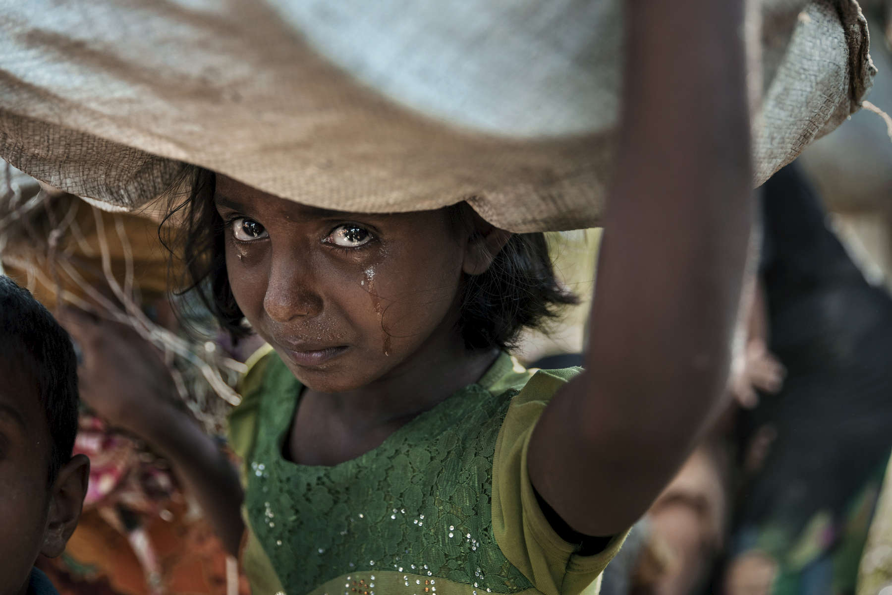 PALONG KHALI, BANGLADESH - OCTOBER 16: A Rohingya girl cries, traumatized after days of walking, with little sleep, as refugees fleeing from Myanmar wait in the hot sun on a muddy rice field near Palang Khali, Cox's Bazar, Bangladesh. Well over a half a million Rohingya refugees have fled into Bangladesh since late August during the outbreak of violence in Rakhine state causing a humanitarian crisis in the region with continued challenges for aid agencies.