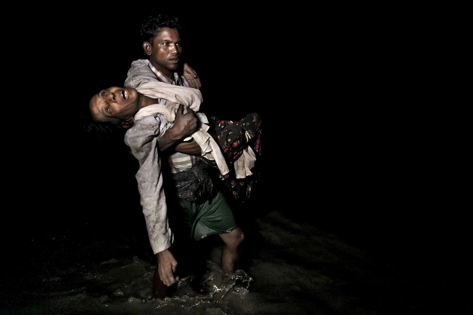 SHAH PORIR DWIP, BANGLADESH - SEPTEMBER 27: Sona Banu gets carried by Nobi Hossain through the shores of the Naf river as hundreds of Rohingya arrive by boats in the safety of darkness September 27, on Shah Porir Dwip island, Cox's Bazar, Bangladesh. Over 655,000 Rohingya refugees have fled into Bangladesh since late August during the outbreak of violence in Rakhine state.The refugee emergency unfolded in late August after an attack on state security forces by Rohingya insurgents, triggering a brutal military crackdown that has forced more than half of the country's 1.1 million population fleeing to neighboring Bangladesh creating the fastest cross-border exodus ever witnessed with over 630,000 new arrivals. Thousands of children who are traveling alone are at serious risk of trafficking and exploitation. Many traumatized refugees arrived telling stories of horror alleging rape, killings and the burning of hundreds of villages, which have been well documented by the media, along with the U.N and various human rights groups.