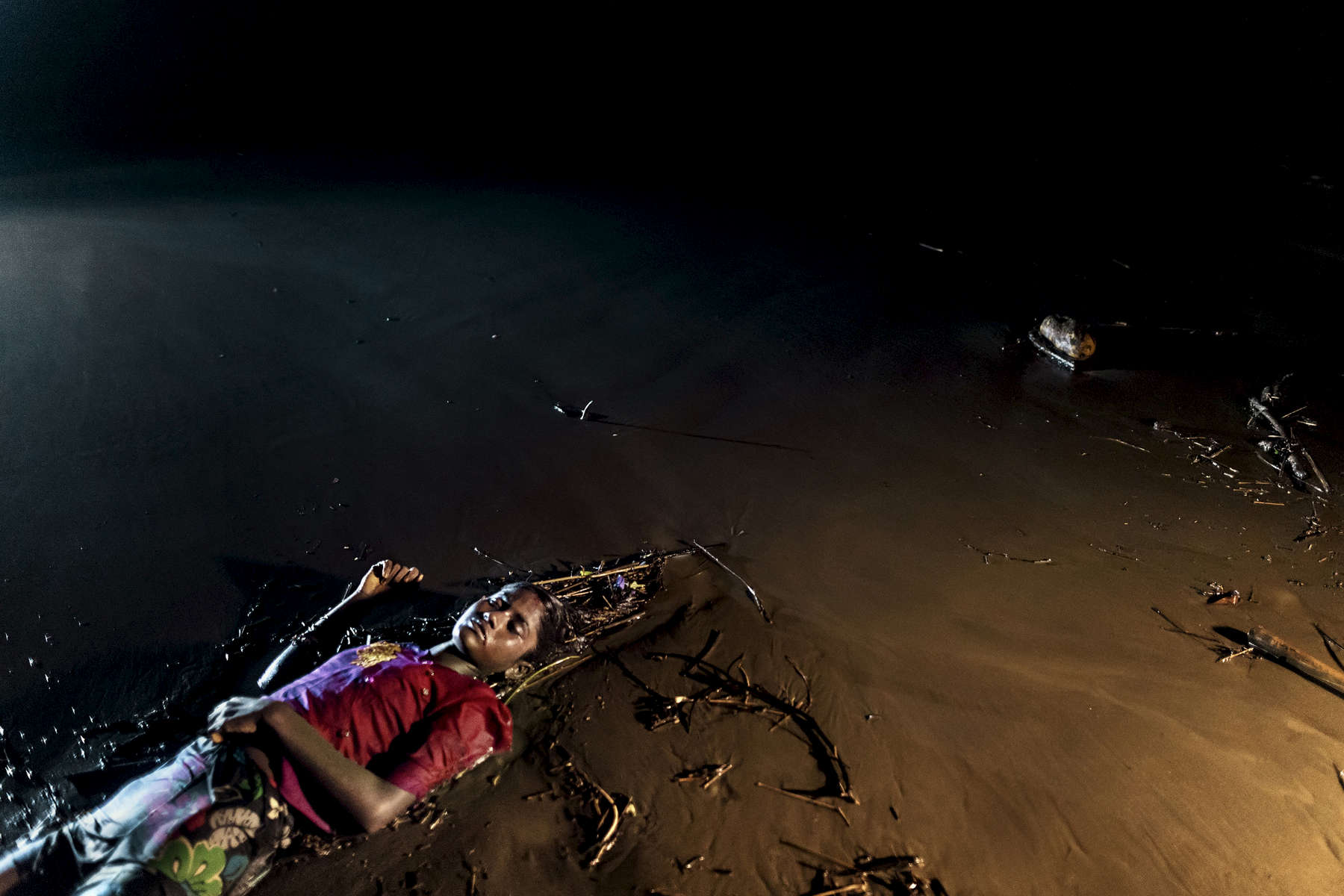 INANI BEACH, BANGLADESH - SEPTEMBER 28: The body of a Rohingya woman lays on a beach washed up after a boat sunk in rough seas off the coast of Bangladesh carrying over 100 people September 28 close to Patuwartek, Inani beach, Bangladesh. Seventeen survivors were found along with the bodies of 15 women and children. Over 655,000 Rohingya refugees have fled into Bangladesh since late August during the outbreak of violence in Rakhine state.
