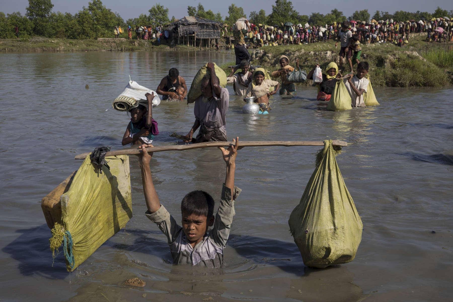 PALONG KHALI, BANGLADESH - OCTOBER 16: Thousands of Rohingya refugees fleeing from Myanmar cross a small stream in the hot sun on a muddy rice field near Palang Khali, Cox's Bazar, Bangladesh. Well over a half a million Rohingya refugees have fled into Bangladesh since late August during the outbreak of violence in Rakhine state causing a humanitarian crisis in the region with continued challenges for aid agencies.