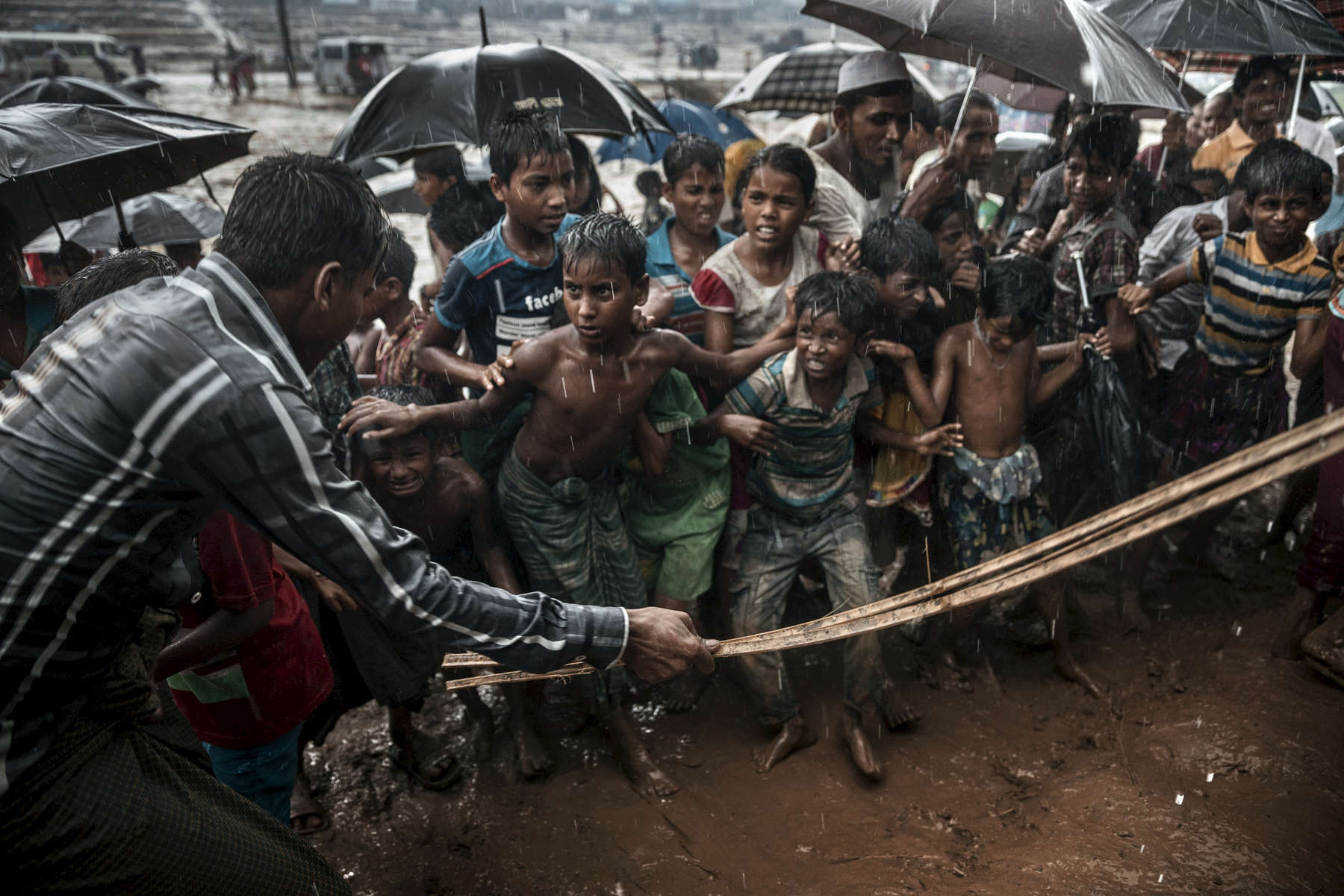 THAINKHALI, BANGLADESH - OCTOBER 7: A man beats anxious Rohingya children as things get out of control during a humanitarian aid distribution while monsoon rains continue to batter the area causing more difficulties October 7, Thainkhali camp, Cox's Bazar, Bangladesh. Well over a half a million Rohingya refugees have fled into Bangladesh since late August during the outbreak of violence in Rakhine state causing a humanitarian crisis in the region with continued challenges for aid agencies.