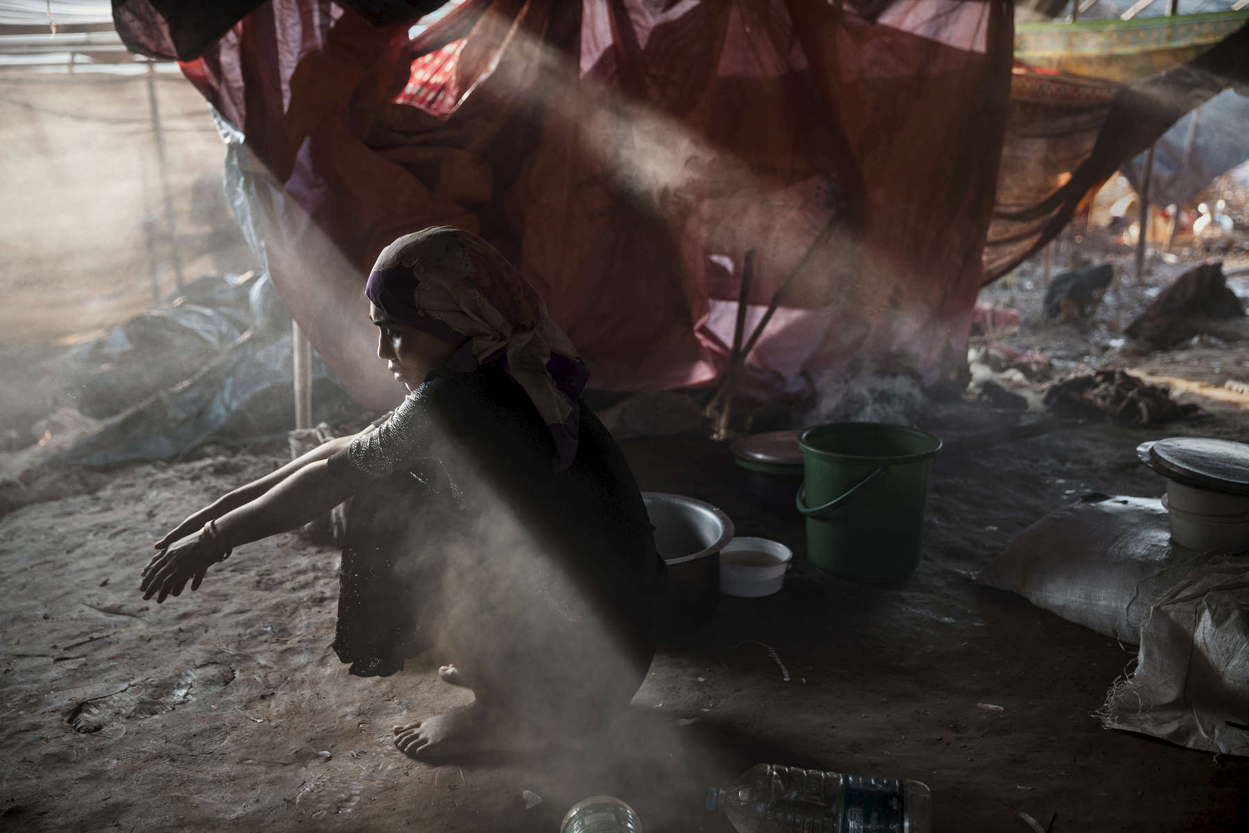 Sajida Begum, 18, sits in her makeshift tent washing rice for dinner as smoke catches the late afternoon light September 25, in Thainkhali camp, Cox's Bazar. The refugee emergency unfolded in late August after an attack on state security forces by Rohingya insurgents, triggering a brutal military crackdown that has forced more than half of the country's 1.1 million population fleeing to neighboring Bangladesh creating the fastest cross-border exodus ever witnessed with over 655,000 new arrivals.