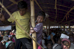 A Rohingya child is caught up in a chaotic scene as aid distribution gets out of control near Balukhali camp.