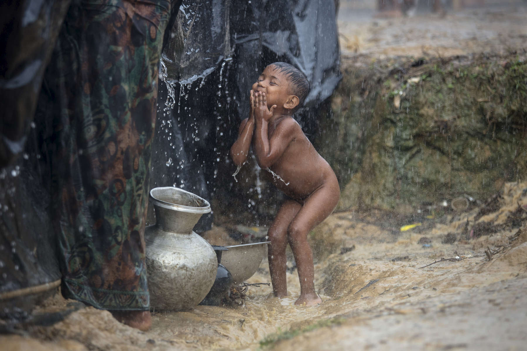 KUTUPALONG, BANGLADESH - OCTOBER 13: A Rohingya boy takes advantage of monsoon rains to bathe himself October 13, in Kutuplaong refugee camp , Cox's Bazar, Bangladesh. For years Buddhist majority Myanmar has struggled to deal with a deeply rooted hatred towards the Rohingya in western Rakhine state. The Muslim ethnic minority were always considered illegal immigrants from Bangladesh and denied the rights of citizenship. The refugee emergency unfolded in late August after an attack on state security forces by Rohingya insurgents, triggering a brutal military crackdown that has forced more than 650,00 of the country fleeing to neighboring Bangladesh creating the fastest cross-border exodus ever witnessed.